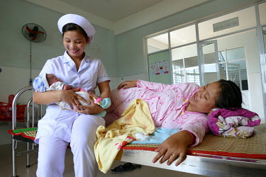 A nurse comforts Nguyen Thi Dieu's (20) newborn boy on a ward in the Department of Obstetrics & Gynecology at Quang Nam General Hospital.