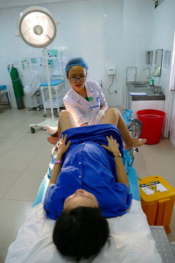 A doctor checks Nguyen Thi Thuy Trang's unborn foetus as she lies on a delivery bed in the Department of Obstetrics & Gynaecology at Quang Nam General Hospital.