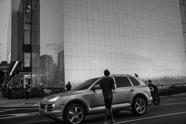A homeless man begs at a car window in front of a luxury shopping centre in Sao Paulo.