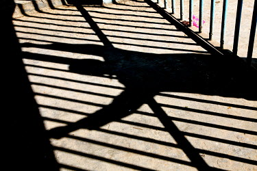 The shadow of an inmate and bars of a prison.
