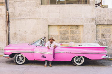 Ronnie Chong, the driver of a 1959 vintage American Chevrolet Impala, painted pink and now used as a taxi taking tourists on city tours.  Since the Cuban government put a heavy focus on tourism to dri...