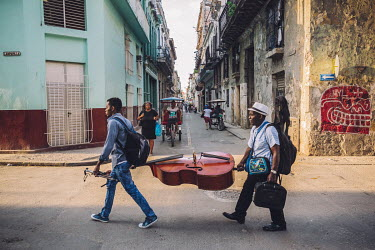 Two musicians walk through the old town carrying a double bass between them.