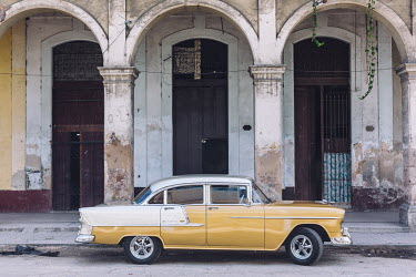 A restored vintage American car parked on Calle Apodaca.  Since the Cuban government put a heavy focus on tourism to drive GDP, taxi drivers (in both classic cars and regular vehicles) have found them...