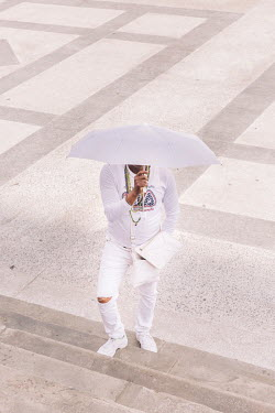 A man in the white clothing of a Santeria initiate (iyawo), holding an umbrella while waiting near Paseo de Mart.   The donning of all-white consecrated garments and other accessories is symbolic for...