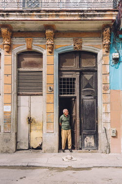 A man stands in the doorway of his residential building in the old town.