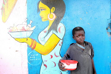 A 'Talibe' (children who study the Koran at a school known as a 'Daara' and must beg or scavenge to feed themselves) begging beside a restaurant mural at a bus station. They are all students of Korani...