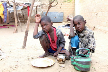 Two 'Talibe' (children who study the Koran at a school known as a 'Daara' and must beg or scavenge to feed themselves) boys rest after spending the day begging for food and money before returning to t...