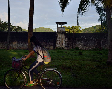 A woman rides her bicycle past the walls of a prison, built by the French colonial authorities and used by the Americans and their allies and the communists.