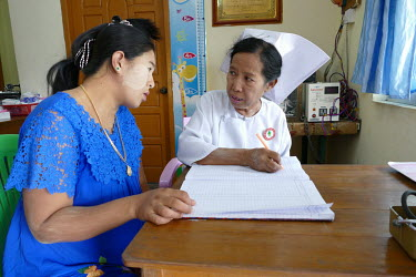 A midwife at the Myanmar Nurse & Midwives Association Nurses' Complex, in consultation with Khin Soe Win (26), pregnant with her second child.