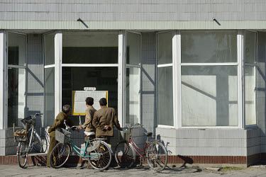 Men reading a newspaper displayed for the public in a window.