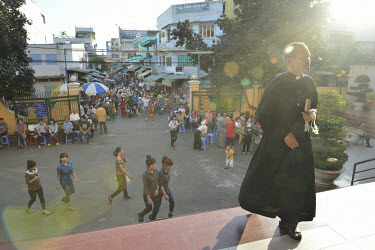 A priest leads the children of the Mai Am Hoa Hue Orphanage to church for their weekly Sunday mass at a church located near the orphanage in district 12.