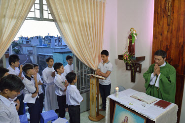 A priest leads children in mass in the Mai Am Hoa Hue Orphanage in district 12.