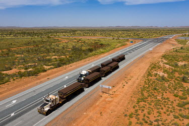 Stationary trucks, known road trains, waiting for a flooded road to open. Several drivers, whose job it is to transport iron ore from a large mine west of Marble bar, were stranded due to a flooded ro...