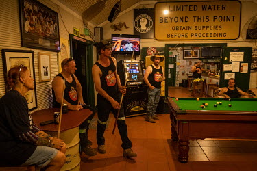 Truck drivers, whose job it is to transport iron ore from a large mine west of Marble Bar, socialise at the non-airconditioned Iron Clad Hotel, the only pub in town. Where a large sign warns customers...