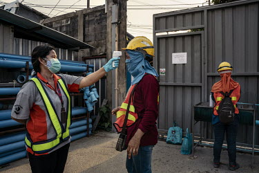 Construction workers, a sector which is largely made up of migrant workers, have their temperatures checked and wash their hands as they arrive back at their dormitories after a day's work.