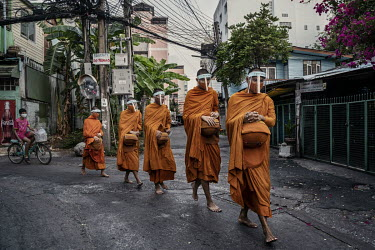 Monks from Wat Matchanthikaram, wearing face masks and face shields as they collect alms from local residents.
