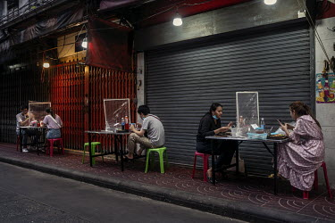 People eat at pavement tables fitted with protective screens at a street food stall.