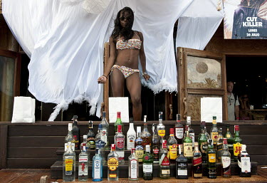 A woman in a bikini dancing at an open air beach bar, behind a collection of bottles of various spirits.
