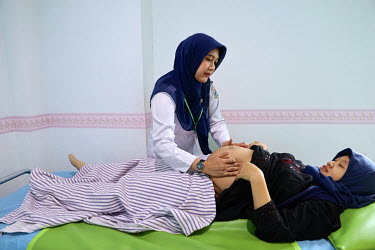 A pregnant woman has her abdomen checked by a health worker at a clinic during an antenatal consultation.
