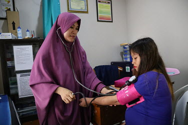 A pregnant woman has her blood pressure measured by a health worker at a community clinic during an antenatal consultation.