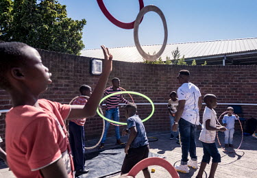 Children practice circus tricks outside a hospital in the township of Khayelitsha. Zip Zap Circus' 'Ubuntu' program aims to introduce children living with HIV to the world of circus.