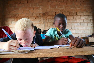 Sergio (9), who is an albino and has issues with his sight, writes in his text book during a class at his school.