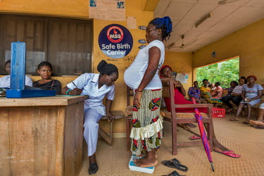 Nurse Mary Ogun records a pregnant client's weight during an examination at the Ewatto community Primary Health Center1.