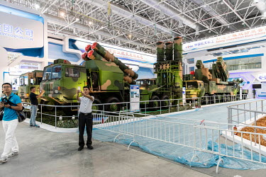 Visitors snap pictures while standing in front of mobile missile and rocket launchers on display at the China International Aviation & Aerospace Exhibition.