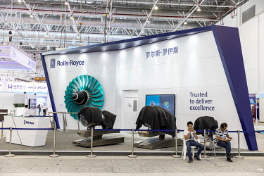 Workers take a break while sitting in in front of covered Rolls-Royce engine models at the China International Aviation & Aerospace Exhibition.
