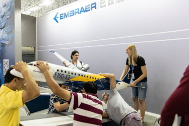 Workers install a model of an Embraer E190-E2 passenger jet at the China International Aviation & Aerospace Exhibition.