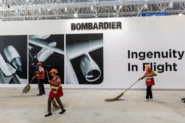 A cleaning crew sweeps past a wall forming part of the Bombardier exhibition booth at the China International Aviation & Aerospace Exhibition.