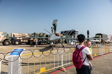 A man carrying a child walks by a Chinese made military drone or Unmanned Arial Vehicle (UAV) displayed at the China International Aviation & Aerospace Exhibition.