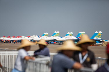 Workers set up a fence near a row of Russian Aircraft Corp. MiG-29 jets sitting on the tarmac at the China International Aviation & Aerospace Exhibition.