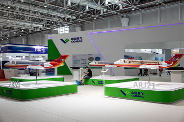 A man sits near Commercial Aircraft Corp. of China (Comac) ARJ21 models at the China International Aviation & Aerospace Exhibition.