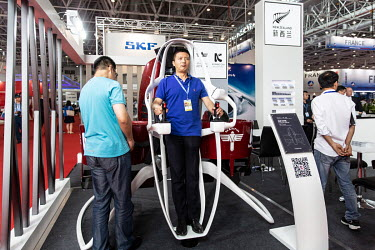 A man stands in a model of a personal aerial vehicle at the China International Aviation & Aerospace Exhibition.