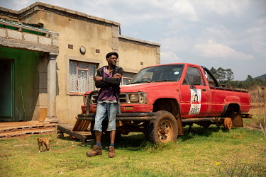 Activist and a farmer, Vusi Matsebula, who was one of the first people in Swaziland to openly disclose on public television that he was HIV positive, stands outside his homestead beside a truck bearin...