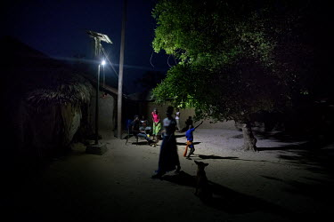 Villagers socialise under bright lights after dark following the installation of a solar power grid paid for by the community which supplies street lighting and, for a monthly subscription, electricit...