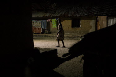A woman is illuminated by a solar powered street lamp as she walks through the village at night.