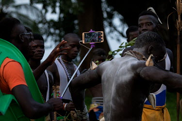 A man films a wrestling bout between teams from the districts of Dome and Ouback. The event will continue into the night as the village has paid for a solar power grid to be installed that supplies st...