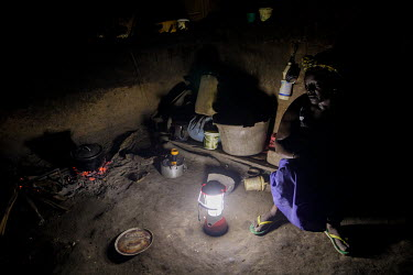 A woman sits in her home beside a pot cooking on an open fire. She has a lamp that can be recharged from the village's solar power grid.