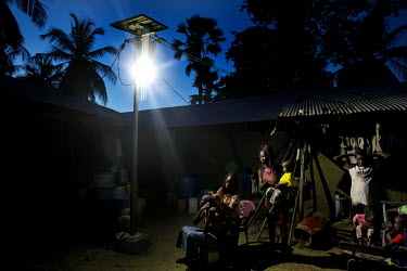 Women style their hair using light from a solar power lamp that is part of a village-wide system that powers street lights and supplies the houses with electricity.