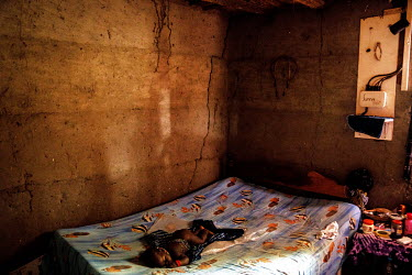 A child sleeps on a bed in a room illuminated by a solar powered lamp, part of a village-wide system that powers street lights and supplies the houses with electricity. To the right of the room the po...