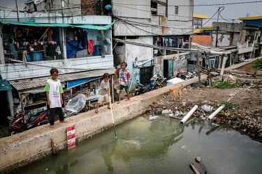 A group of boys use a net in a deep pool of water that has formed behind a secondary wall protecting shops and homes from being inundated by sea water in Pluit, one of Jakarta's most flood-affected ne...