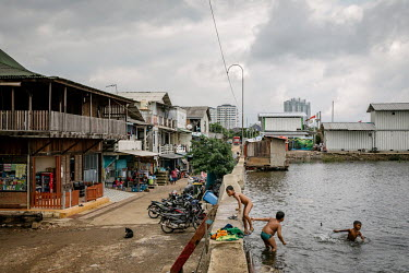A group of boys swimming in sea water that has formed behind a secondary wall protecting shops and homes from being inundated in Pluit, one of Jakarta's most flood-affected neighbourhoods. Due to risi...