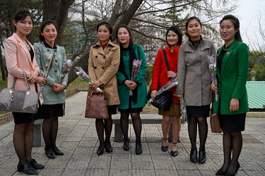 A group of women with flowers purchased from a kiosk at the bottom of Mansudae Hill where they have come to see the giant bronze statutes of Kim Il-sung and Kim Jong-il on the eve of the national holi...