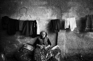 A gipsy woman selling second hand clothes smokes a cigarette while waiting for customers at flee market.