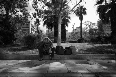 A homeless man sits on the pavement outside a metro station.