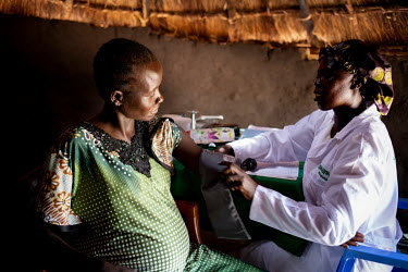 Pregnant Arek Mabior (28) has her blood pressure measured during a consultation with midwife Rebekka at a mobile health clinic in a remote rural area of Aweil. Arek has eight children and is nine mont...