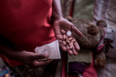 Gabatswane Rodgers (44) displays a handful antiretroviral pills at her home in Selibe Phikwe. Rodgers, a former sex-worker, must support her family on just 600 Pula (GBP 40.00) per month, her salary a...