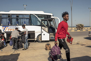 Migrants gather their luggage after arriving by coach at Tripoli's airport where they are due to be flown to an UNHCR (United Nations High Commissioner for Refugees) relocation centre in Niamey, Niger...
